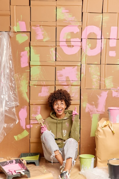 Hey look what i did! cheerful dark skinned ethnic woman points above and shows how she painted walls in apartment surrounded with paint tools busy doing repairing at home and room redecoration