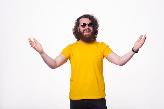 반가워요, 노란색 티셔츠를 입은 수염난 힙스터 남자가 환영 제스처를 취합니다
