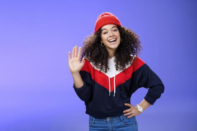 こんにちはと手を振っている巻き毛のかわいい赤いビーニーの魅力的な女性のスキーソファに会えてうれしいです...
