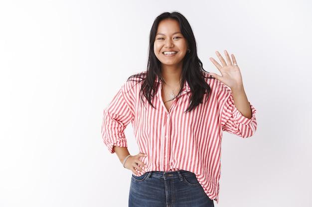 Привет, друзья, как дела. дружелюбная и общительная милая очаровательная азиатская женщина в полосатой блузке приветствует новичков, радостно машет рукой в жесте приветствия или приветствия, широко улыбаясь в камеру над белой стеной