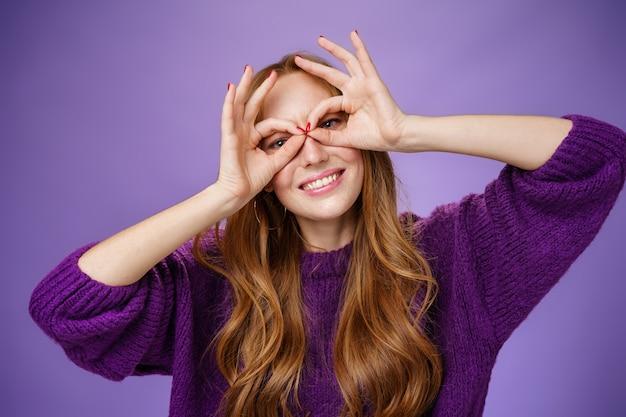 Ehi, sorridi di più. ritratto di ragazza rossa affascinante brillante e divertente in maglione viola che fa maschera con le mani sugli occhi e sorride ampiamente agendo come un supereroe in posa eccitato e giocoso.