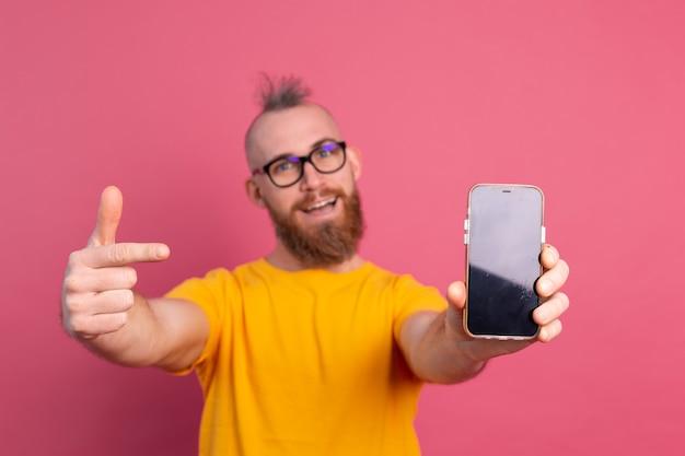 이봐 새로운 것. 분홍색에 검은 색 빈 화면으로 자신의 휴대 전화를 가리키는 행복 유럽 수염 난된 남자