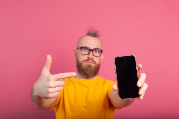 Hey qualcosa di nuovo. ragazzo barbuto europeo arrabbiato serio che indica il suo telefono cellulare con lo schermo in bianco nero sul colore rosa