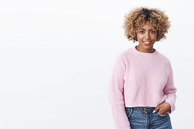 Эй, что ты делаешь. портрет общительной дружелюбной стильной афро-американской женщины со светлой вьющейся прической, держащей руку в кармане, стоящей в расслабленной прохладной позе и широко улыбающейся в камеру