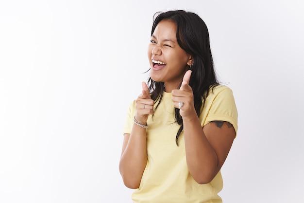 Ehi, cosa c'è. amichevole ed estroversa spensierata giocosa ragazza tatuata polinesiana in maglietta gialla che fa pistole con le dita e punta alla telecamera strizzando l'occhio, suggerendo di prenderti su sfondo bianco