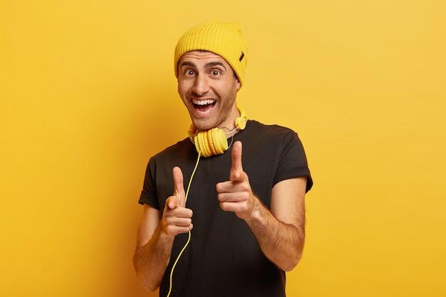 Ehi, sei scelto! felice uomo allegro punta il dito indice alla fotocamera