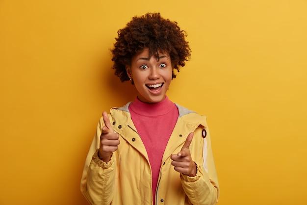 Ehi tu, attenzione. concetto di scelta dei clienti. la ragazza afroamericana positiva indica con l'espressione felice, sceglie qualcosa, sceglie qualcuno, indossa abiti casual, isolato sulla parete gialla