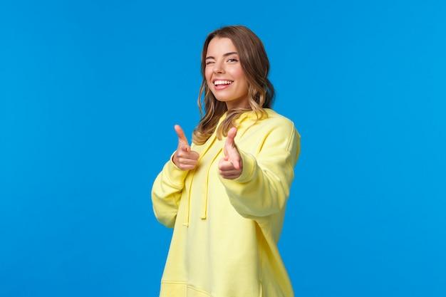 Эй, ты. дерзкая и беспечальная милая современная европейская девушка в желтом hoodie, wink и делает жесты пистолетов пальца на камере для того чтобы сказать высокую, неофициальную концепцию приветствию.