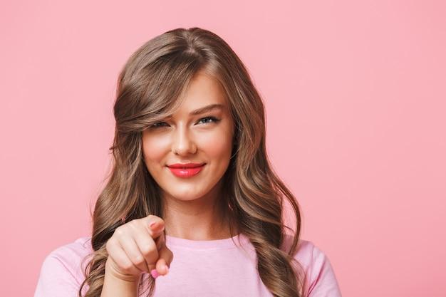 ねえ!ピンクの背景に分離されたカメラと人差し指を見て長い巻き毛の茶色の髪と軽薄な素敵な女性のクローズアップ写真