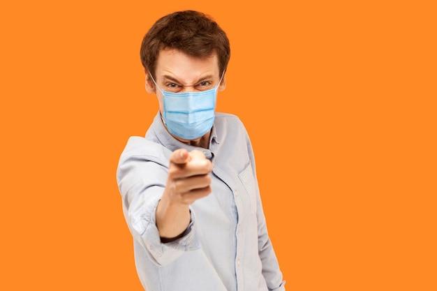 ねえ。怒った若い労働者の肖像画は、狂った顔でカメラを指して叱るサージカルマスクを立っています。オレンジ色の背景に分離された屋内スタジオショット。