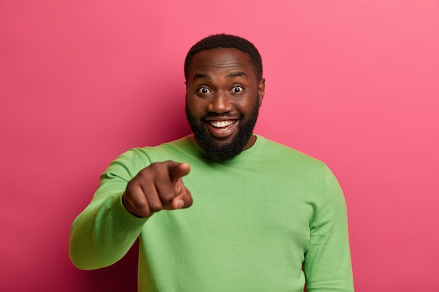 Hey, you. positive bearded black man points index finger at camera, smiles happily and chooses someone, wears pastel green jumper