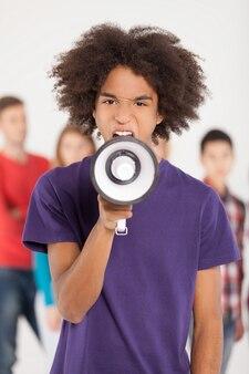 Эй, ты! молодой африканский подросток кричит в мегафон, пока его друзья стоят на заднем плане