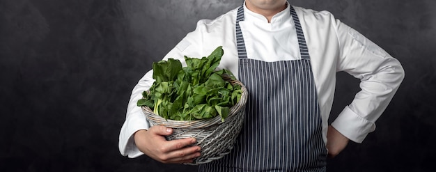 Hhand is holding basket with green salad