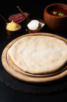 Тесто для пиццы hhomemade на деревянной доске на черном фоне