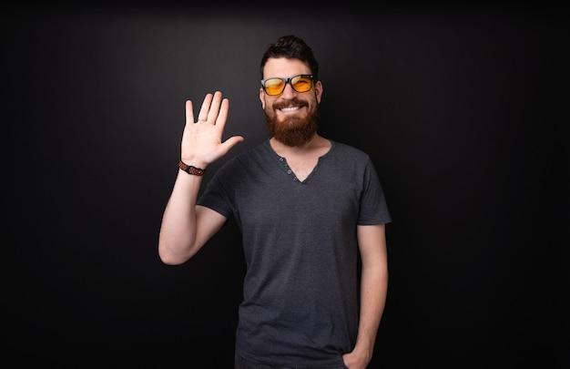 こんにちは、おい!暗い背景の上で敬礼ジェスチャーをしているハンサムなひげを生やした男の写真