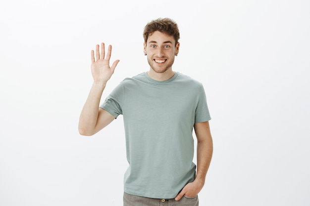 Hi nice to meet you. portrait of handsome outgoing european guy in casual t-shirt raising hand and waving palm in hello gesture