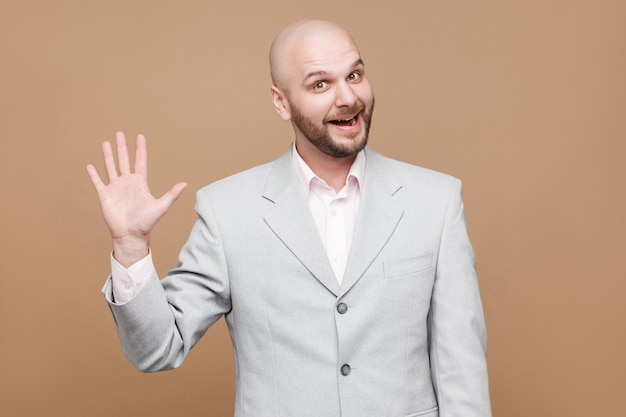 Hi, nice to see you. portrait of handsome funny happy middle aged bald bearded businessman in classic light gray suit standing and looking at camera with greeting hand. isolated on brown background.