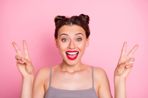 Привет, тусовщики! фотография удивительной молодой девушки смешные булочки красная помада, показывающая символ v-знака, носить повседневную серую майку изолированного розового цвета