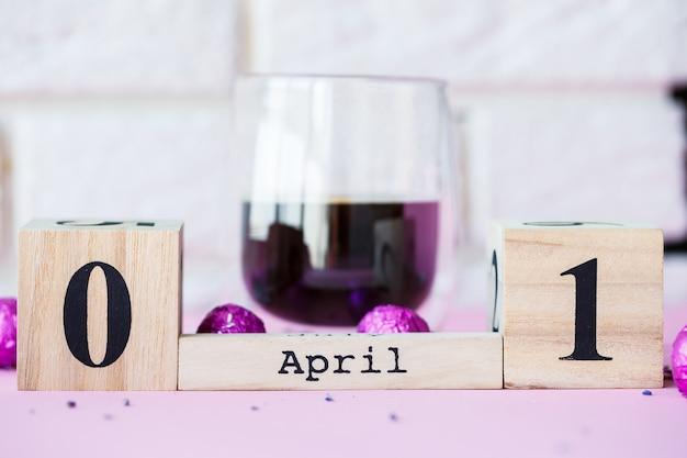 Привет весна. деревянный календарь с датой 1 апреля на розовом фоне. всемирный день смеха