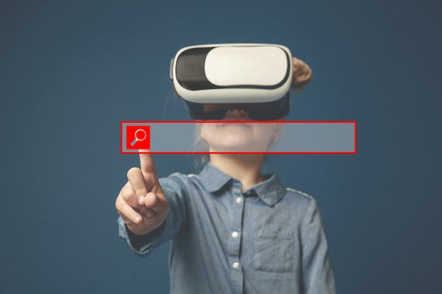 Hi-tech is so close. little girl or child pointing to the empty search bar with vr-glasses isolated on blue studio background. copy space. concept of cutting edge technology, video games, innovation.