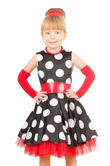 こんにちは。白で隔離された水玉模様のドレスを着て笑っている小さな美しい女の子の肖像画