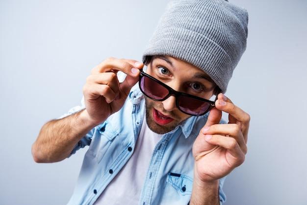 やあ!彼のサングラスを調整し、灰色の背景に立ってカメラを見ている面白い若い男の上面図