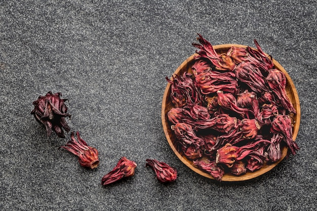 Hibiscus dried flowers in wooden bowl on black background.