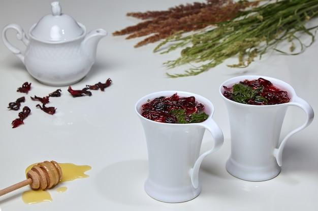 Травяной чай гибискус из суданской розы и цветов мяты в элегантных белых чашках на белом столе в окружении меда, чайника и букета диких трав