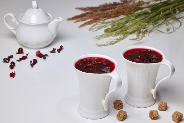スーダンのバラとミントの花から作られたハイビスカスハーブティーと、エレガントな白いカップの砂糖ニッパー