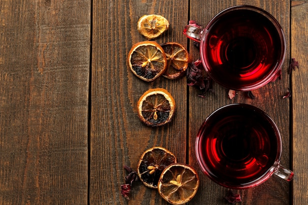 갈색 나무 테이블에 유리 컵에 히비스커스 홍차. 따뜻한 음료. 가을 또는 겨울 음료. 평면도