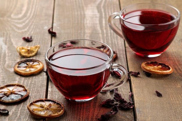 갈색 나무 테이블에 유리 컵에 히비스커스 홍차. 따뜻한 음료. 가을 또는 겨울 음료