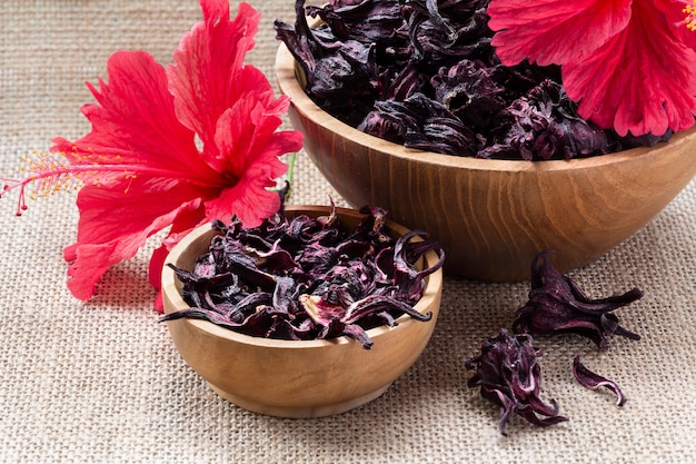 Hibiscus (roselle, karkade) dry flowers in wooden bowl on burlap background.