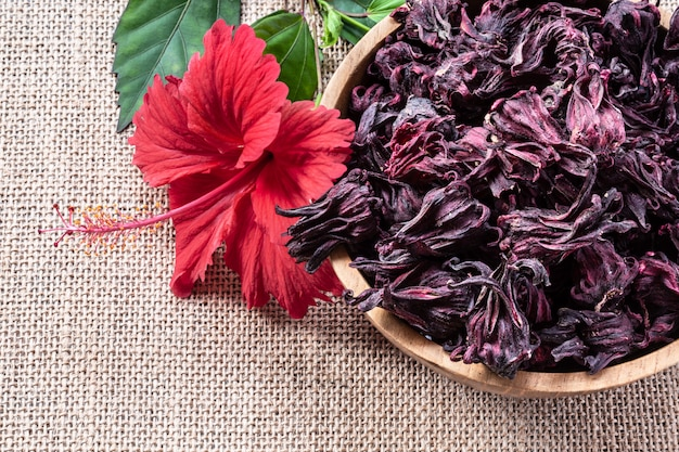 Hibiscus (roselle, karkade) tea in wooden bowl on burlap background with copyspace top view.