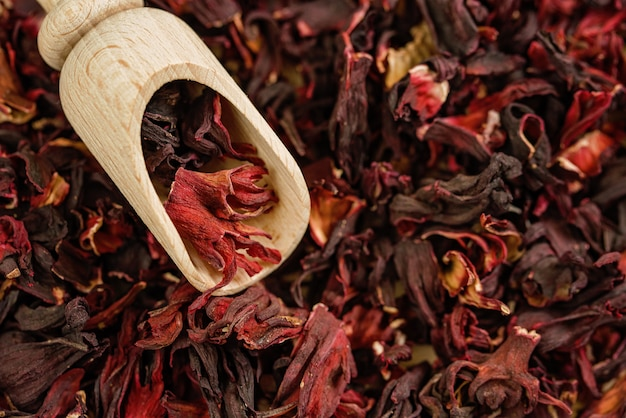 Hibiscus tea. close up. top view. vitamin tea for cold and flu. petals of tea on wooden spoon.