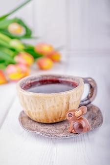 ハイビスカスティー、高級チョコレート、キャンディーバニー、春の花のオレンジ色のチューリップ