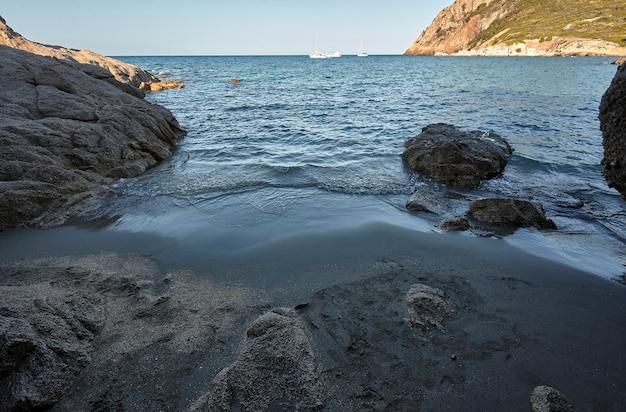 サルデーニャ南部の自然の洞窟の出口にある岩の間の隠れたビーチ