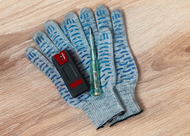 Hidden wiring detector, screwdriver tester and protective gloves out on the table