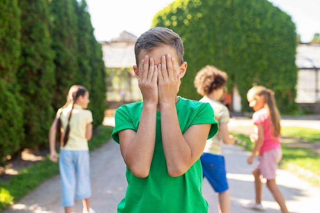 숨바꼭질. 녹색 티셔츠를 입은 소년은 손으로 눈을 가리고 좋은 오후에 공원 뒤에 아이들을 숨깁니다