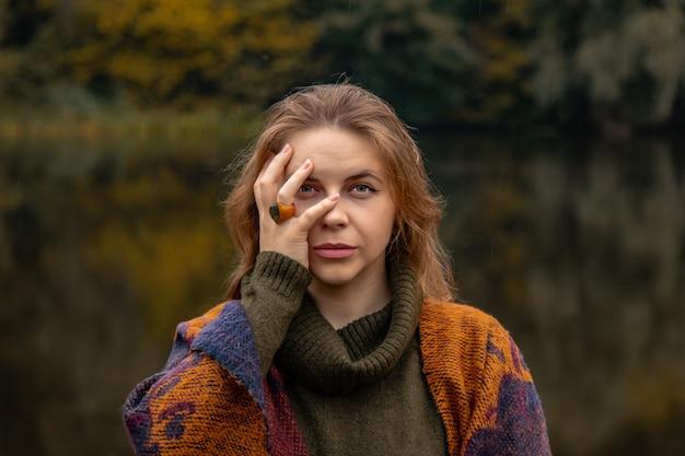 숨바꼭질. 소녀는 그녀의 손으로 그녀의 얼굴을 가렸다. 호수에 근접 초상화 여성의 고통, 슬픔, 폭력, 우울증, 외로움의 개념.