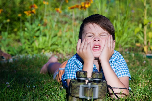 Hide and seek. the boy squeezes his eyes and counts to 10. the binocular lies in front of the child