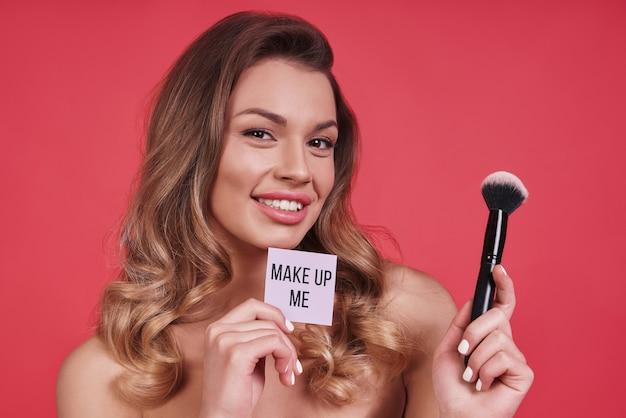 すべての欠陥を隠す。ピンクの背景に立っている間笑顔と化粧ブラシを適用する美しい若い女性