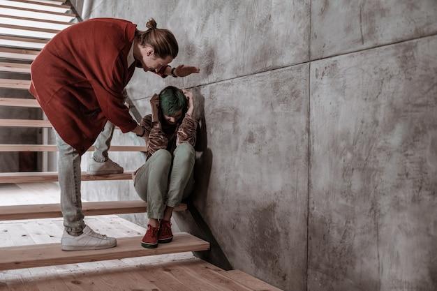 顔隠し。積極的な神経質な男が、階段に座って彼女の顔を隠している彼のガールフレンドを打ち負かした
