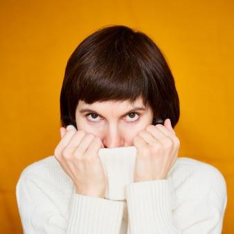 Скрывая лицо за воротником свитера в теплой одежде, женщина средних лет на ярко-желтой стене