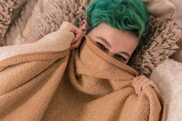 顔隠し。朝、ベッドに横たわる格子縞の後ろに顔を隠している緑髪の陽気な女性