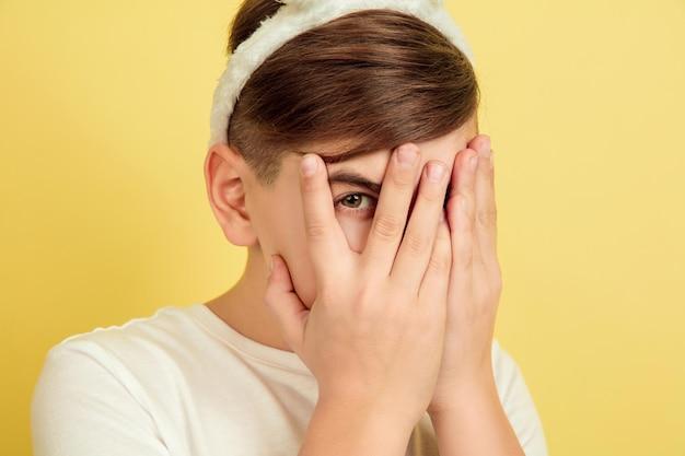 Nascondere il viso nelle mani. ragazzo caucasico come un coniglietto di pasqua su sfondo giallo studio. auguri di buona pasqua.
