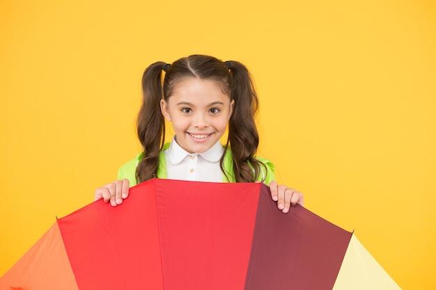 Прячась от дождя. улыбающаяся школьница выглядывает из красочного зонтика. осенний дождь. идти в школу дождливыми днями веселее с яркими аксессуарами. водонепроницаемая одежда. символ защиты.