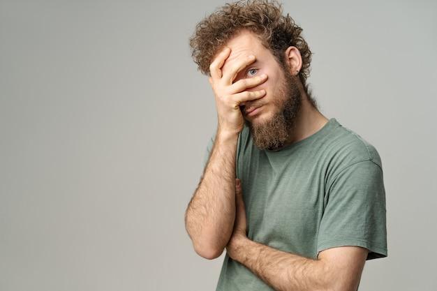Спрятавшийся красивый молодой человек закрыл лицо рукой, глазом, вьющиеся волосы в оливковой футболке изолированы