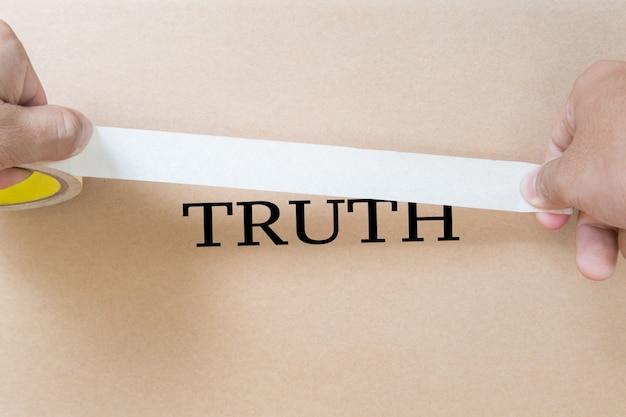 真実を隠すためにテープを持っている手で問題の概念を隠す