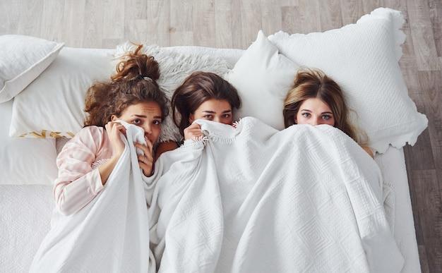 Прячась под одеялом. счастливые подруги хорошо проводят время на пижамной вечеринке в спальне.