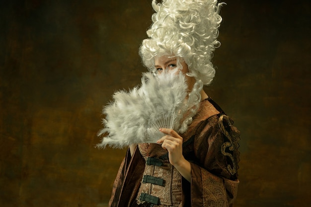 Hiding with fluffy fan. portrait of medieval young woman in brown vintage clothing on dark background. female model as a duchess, royal person. concept of comparison of eras, modern, fashion, beauty.
